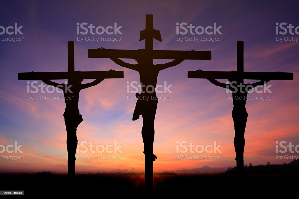 Jesus on cross wtih two prisons in sunrise sky stock photo