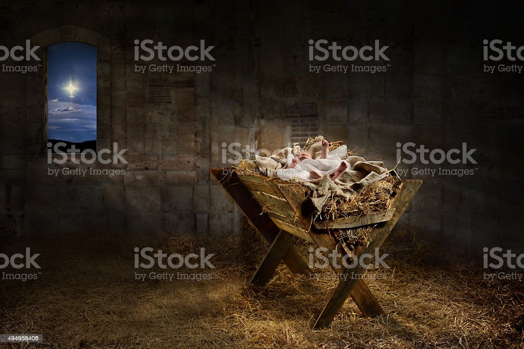 Jesus resting on a manger while light from the star filters into the...