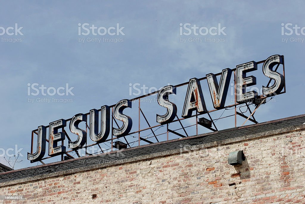 Jesus Saves light-up sign in sky over an old brick building stock photo