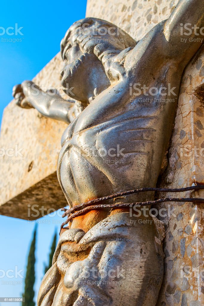 Jesus tied to a cross in graveyard stock photo