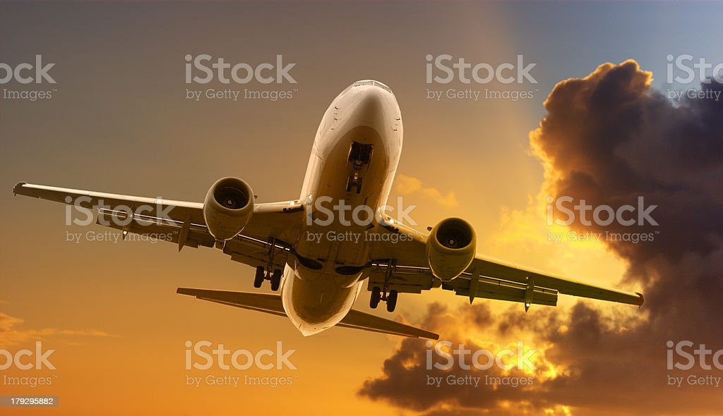 Jet Aeroplane Flying in Bright Sunset Sky Sun Rays stock photo