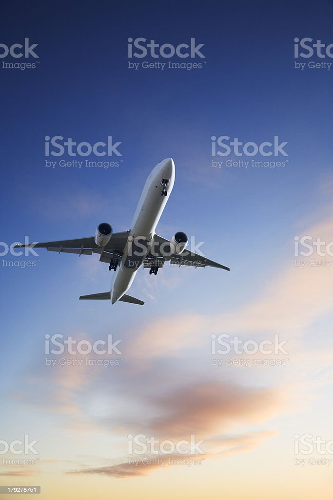 Jet Aeroplane Landing from Bright Sunset Sky Blue Orange Vertical royalty-free stock photo