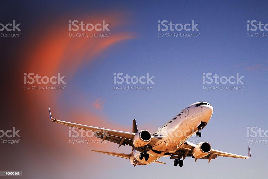 Jet Aeroplane Landing From Bright Twilight Sunset Sky stock photo