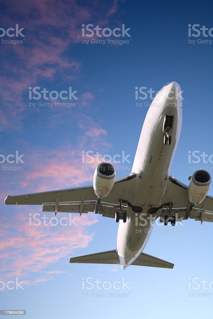 Jet Aeroplane Landing From Bright Twilight Sunset Sky Vertical stock photo