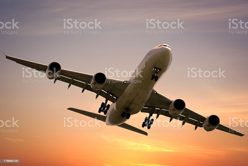 Jet Aeroplane Taking Off into Bright Sunset Sky royalty-free stock photo