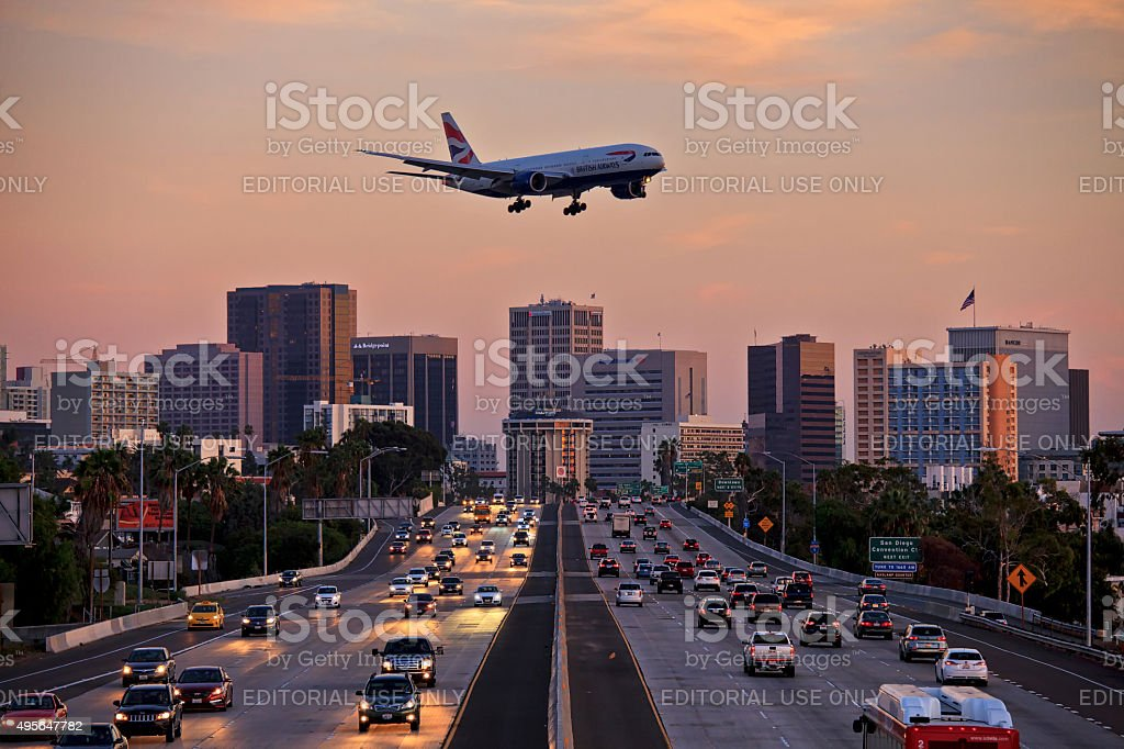 Jet aircraft on landing approach flying low over city freeway stock photo