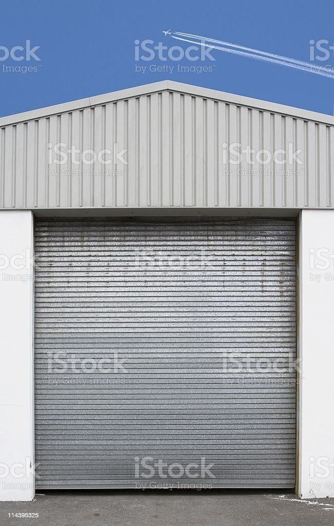 Jet Airliner In Blue Sky Above Factory Building stock photo