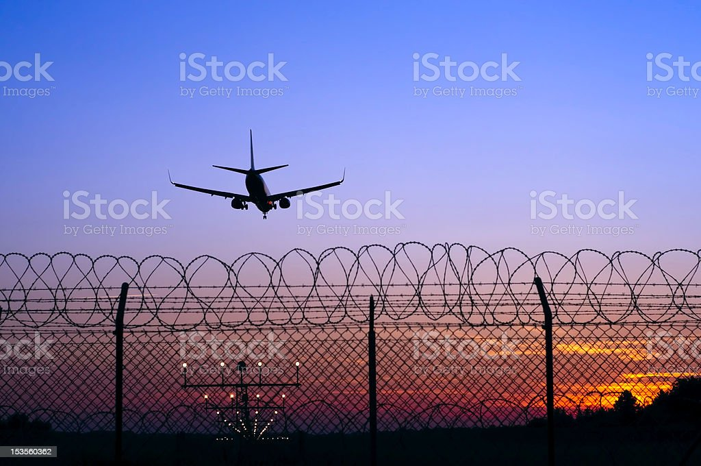 Jet airplane in the distance landing at sunset behind fence stock photo