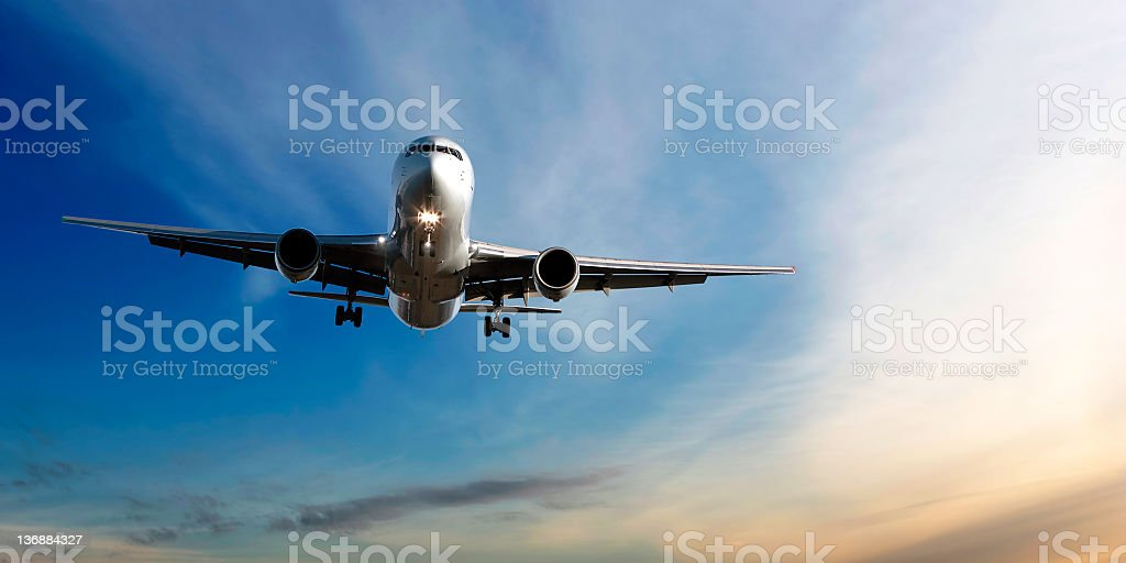 jet airplane landing at dusk royalty-free stock photo