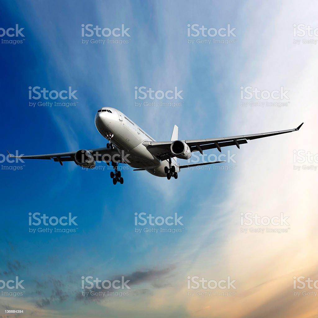 jet airplane landing at dusk stock photo