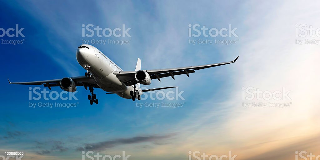 XL jet airplane landing at dusk stock photo