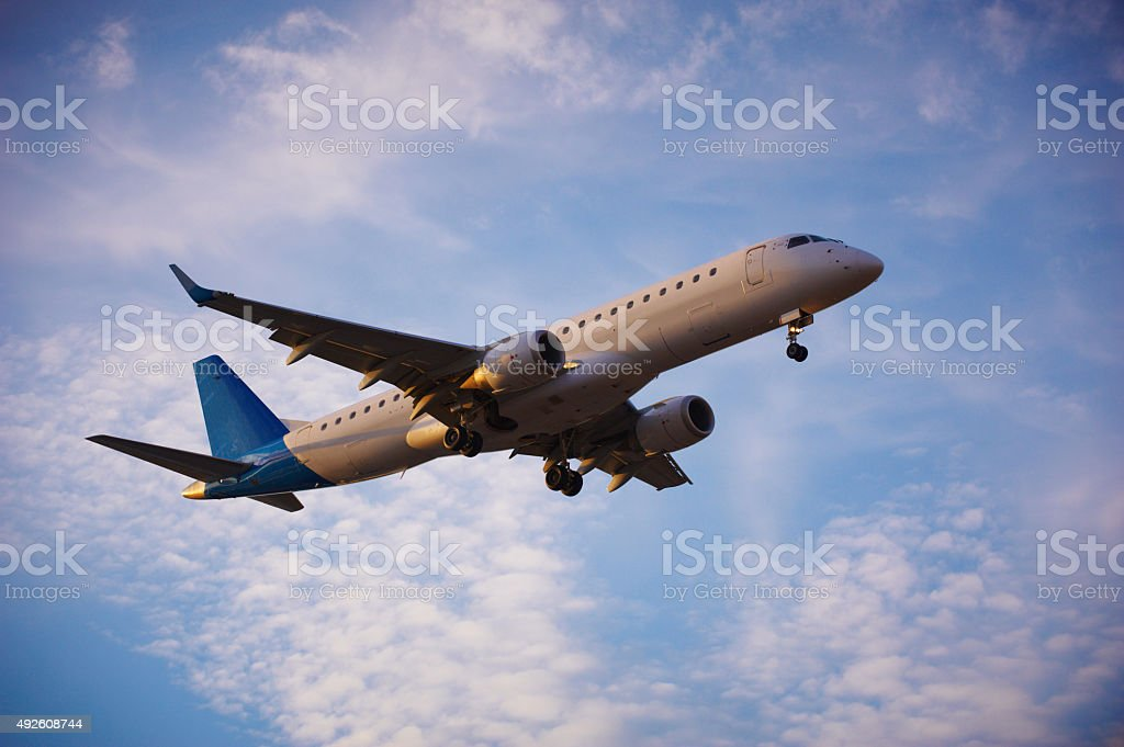 jet airplane landing at evening stock photo