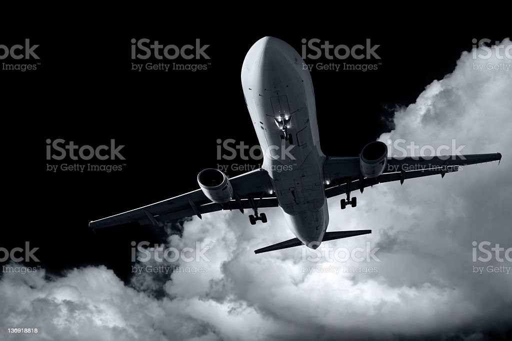 XL jet airplane landing at night stock photo