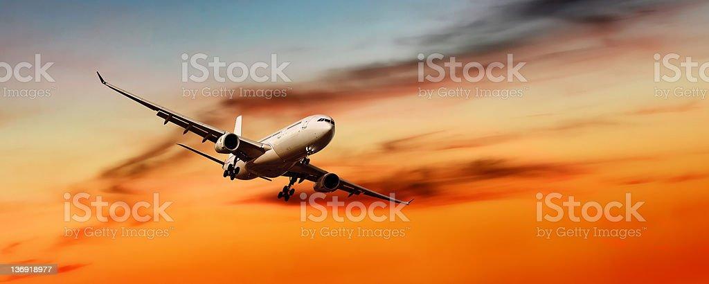 XL jet airplane landing at sunset royalty-free stock photo