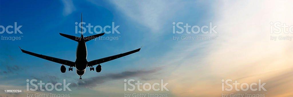 XL jet airplane landing at sunset stock photo