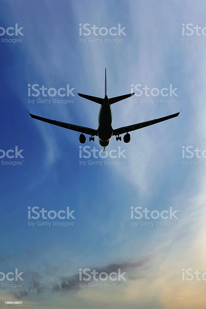 XL jet airplane landing at sunset royalty-free stock photo