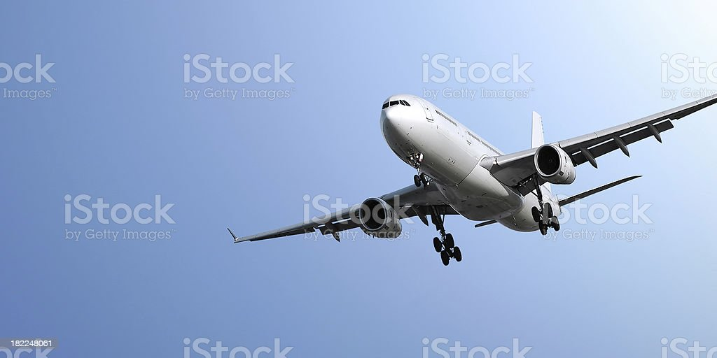 jet airplane landing in blue sky royalty-free stock photo
