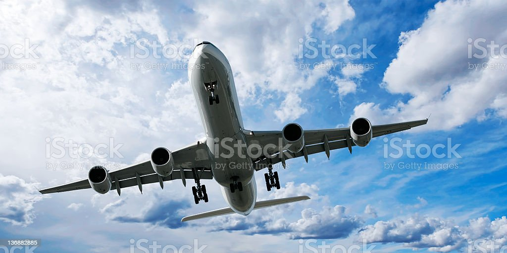 jet airplane landing in bright sky royalty-free stock photo