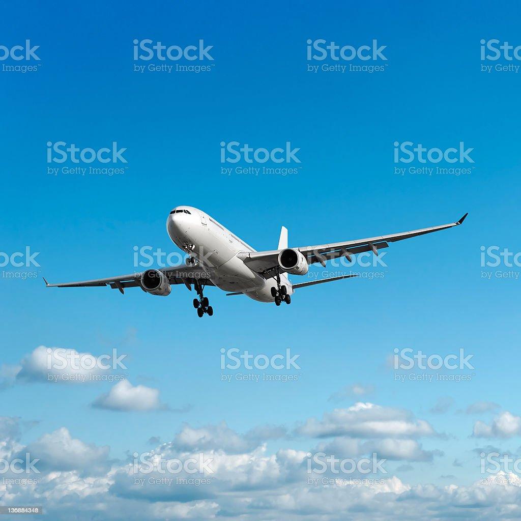 jet airplane landing in bright sky stock photo