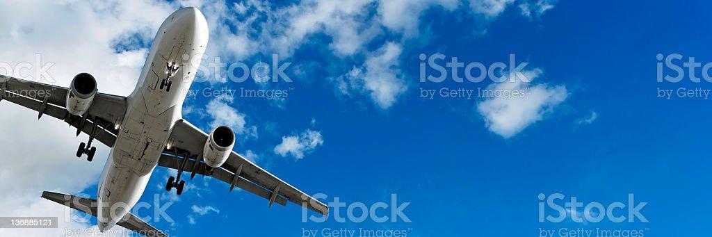 XL jet airplane landing in bright sky stock photo