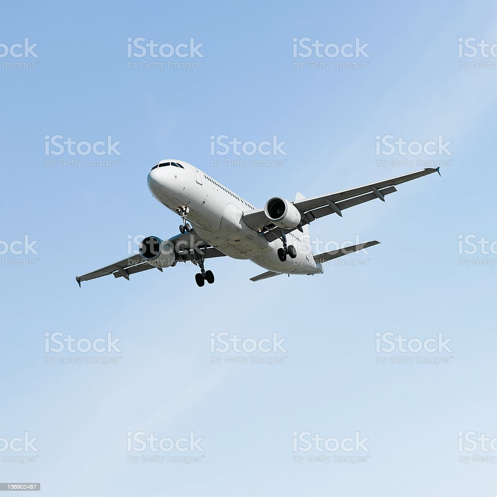 XXL jet airplane landing in bright sky stock photo