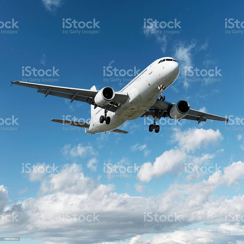 XL jet airplane landing in bright sky stock photo