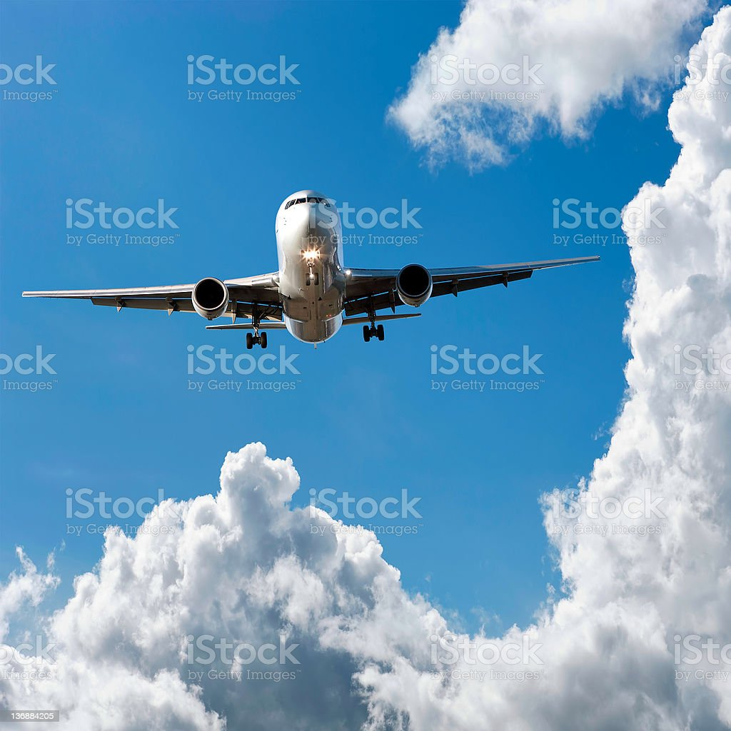 jet airplane landing in cloudy sky royalty-free stock photo