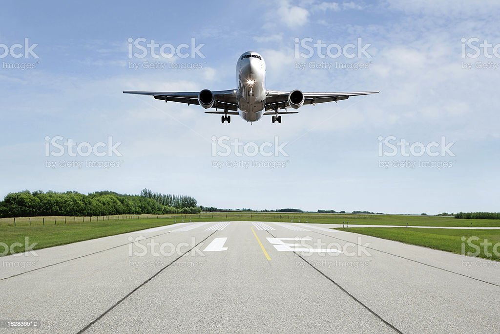 XL jet airplane landing on runway stock photo