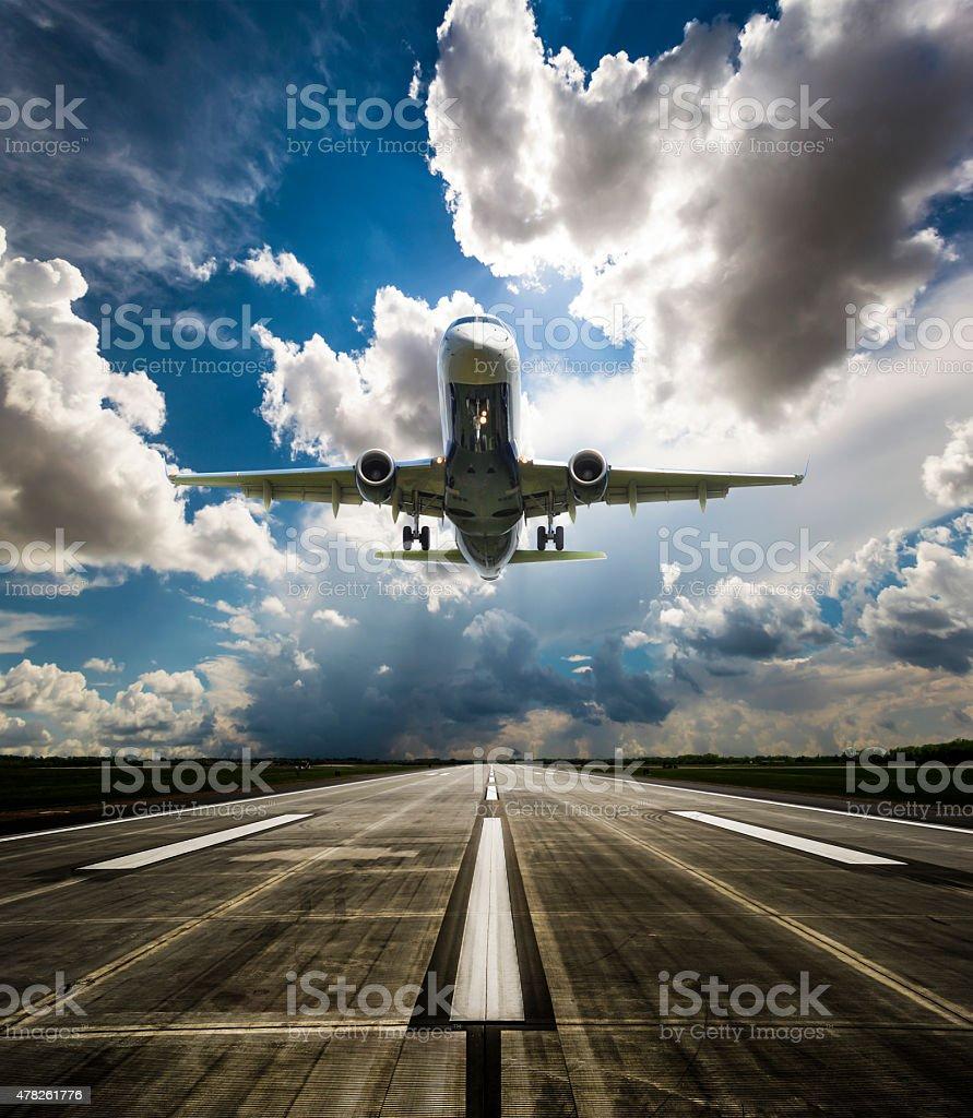Jet airplane landing on runway stock photo
