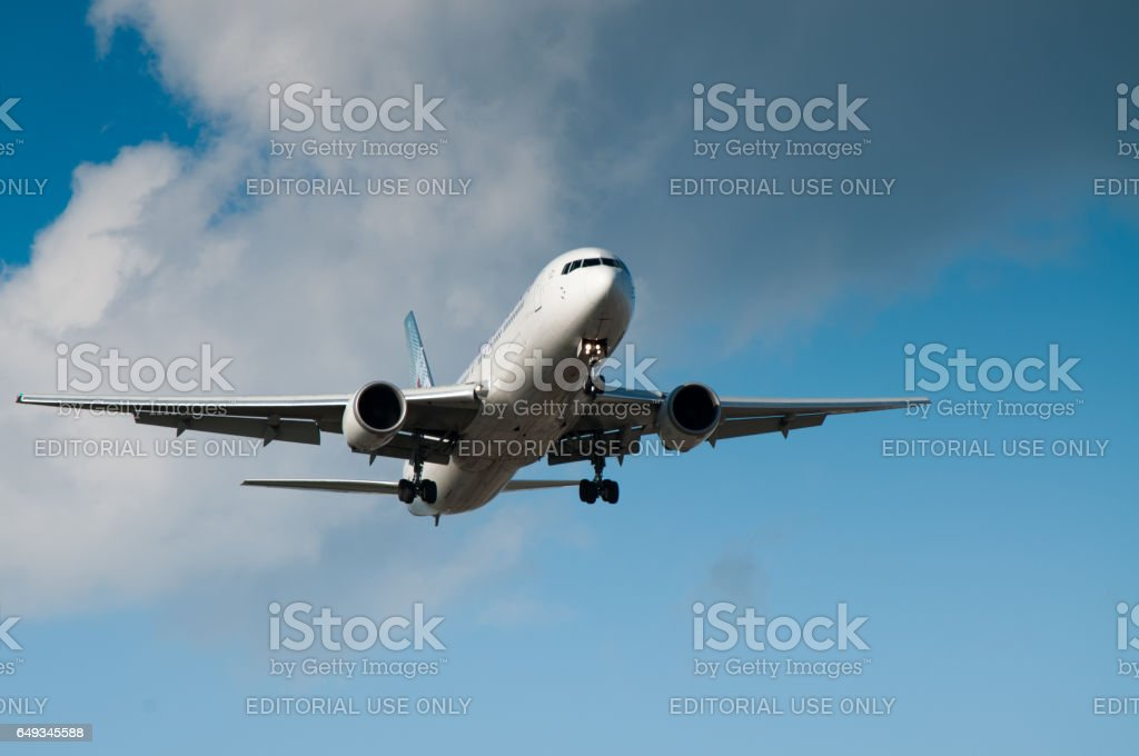 Jet airplane seen from below against a blue sky stock photo