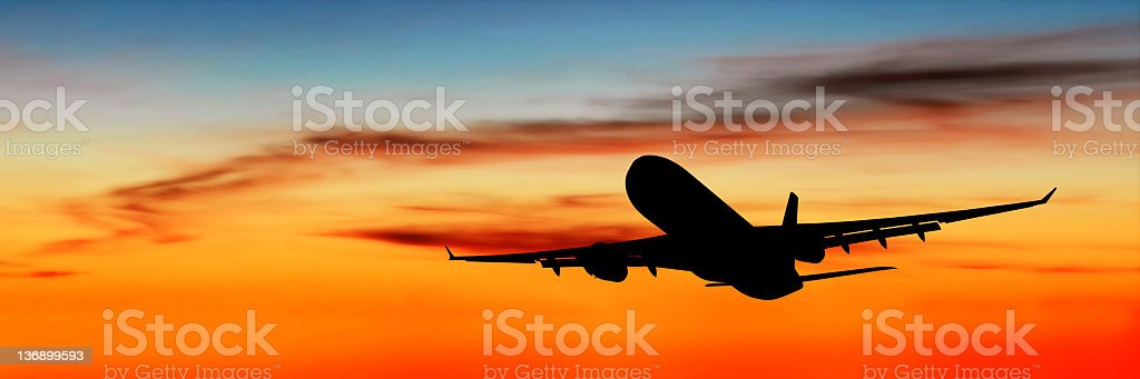 XL jet airplane taking off at dusk stock photo