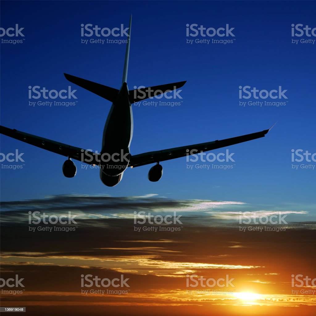 jet airplane taking off at sunset stock photo