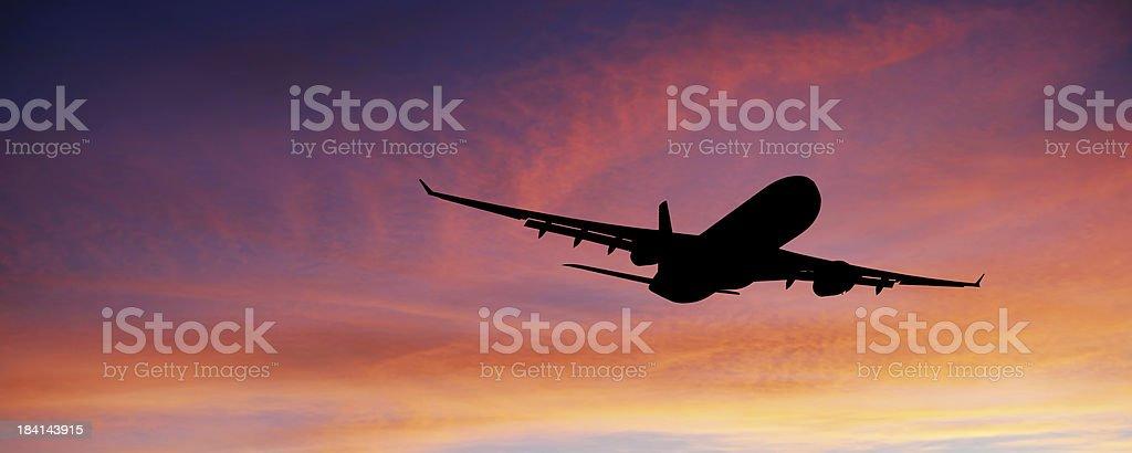 XL jet airplane taking off at sunset stock photo