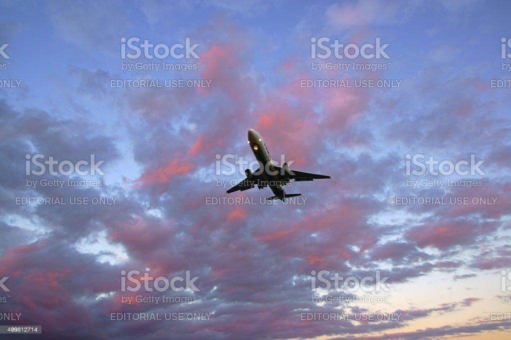 Jet cargo airplane landing at sunset stock photo