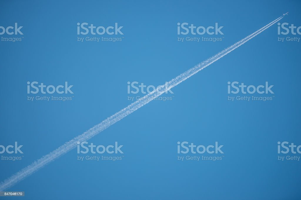 Jet Contrail across a Clear Blue Sky stock photo