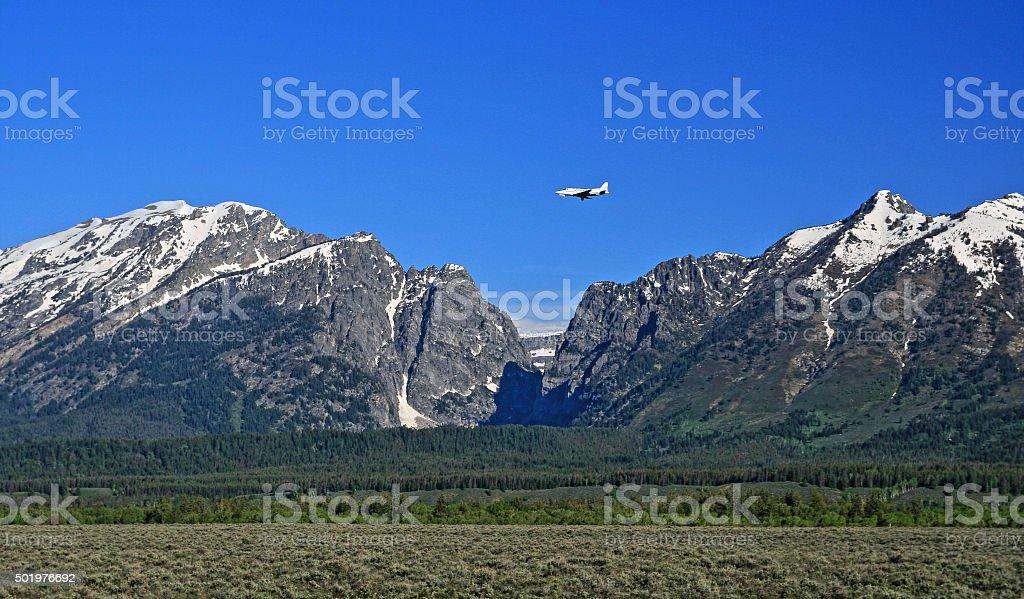 Jet flying into Jackson Airport Grand Tetons Mountain Range stock photo