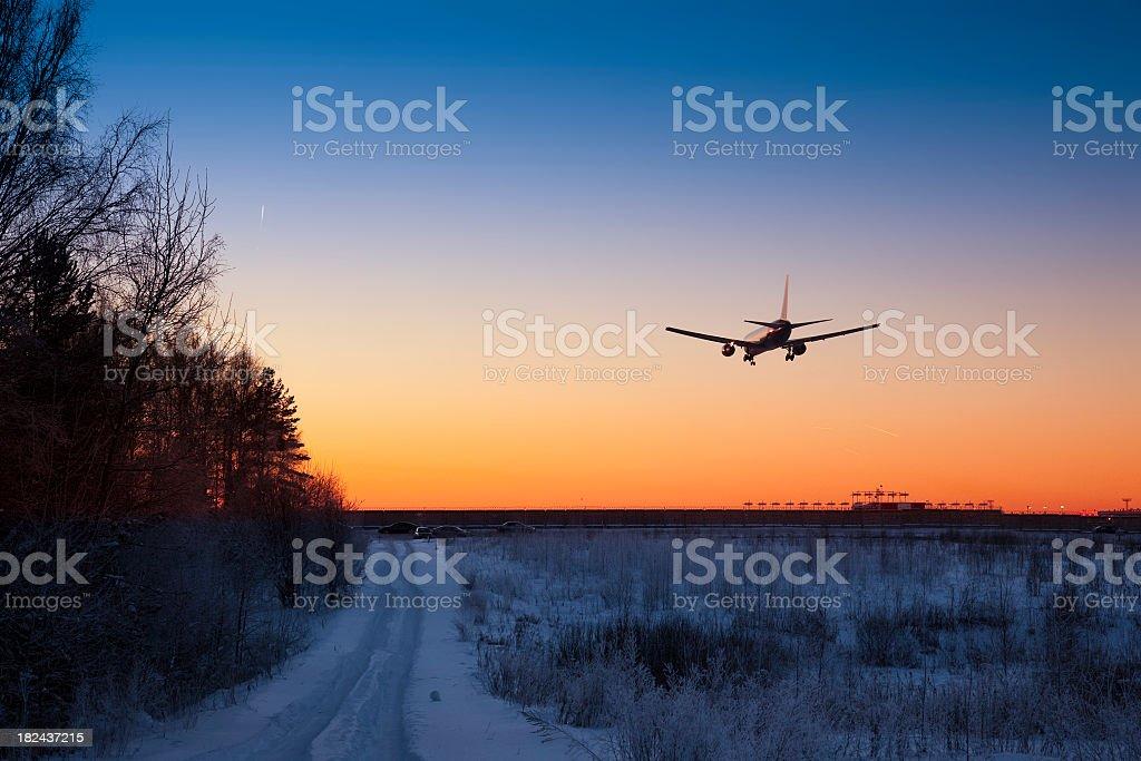 Jet passenger liner landing at sunset stock photo