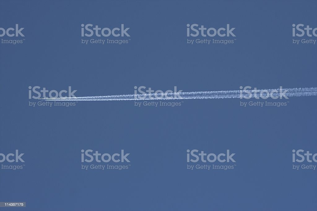 Jet Trail Across Blue Spring Sky royalty-free stock photo