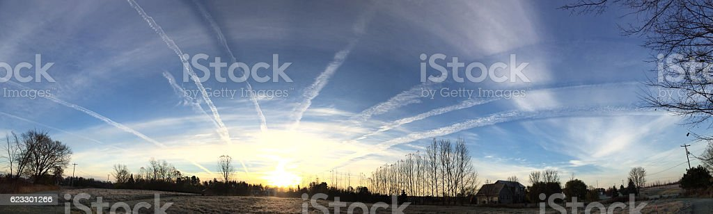 Jet trails fill the morning sky, converging on the sunrise stock photo