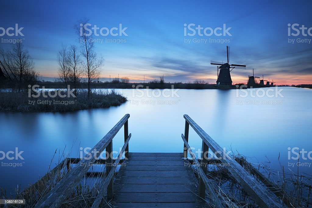 Jetty and traditional windmills at sunrise, Kinderdijk, The Netherlands royalty-free stock photo