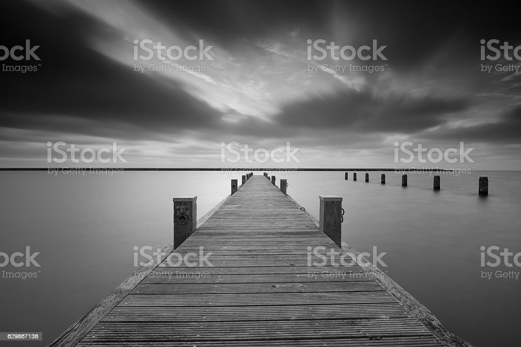 Jetty at lake Markermeer in black and white. stock photo