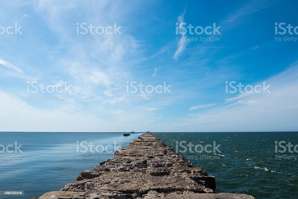 Jetty dividing sea into rough and calm water stock photo