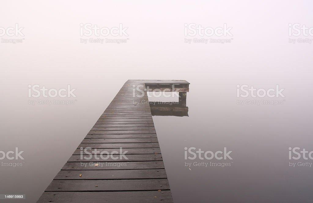 Jetty in autumn fog royalty-free stock photo
