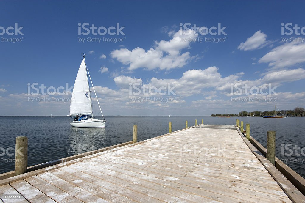 Jetty lakeside with white yacht and magestic cloudscape (XL) royalty-free stock photo