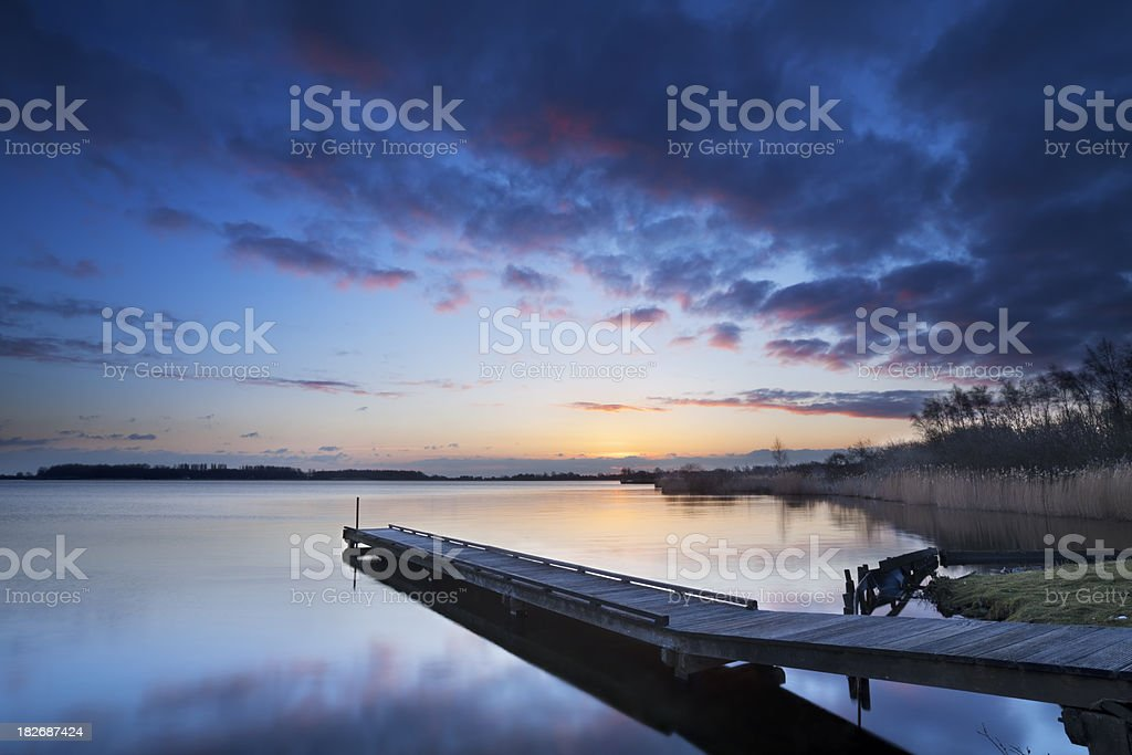 Jetty on a lake at sunrise, near Amsterdam The Netherlands royalty-free stock photo