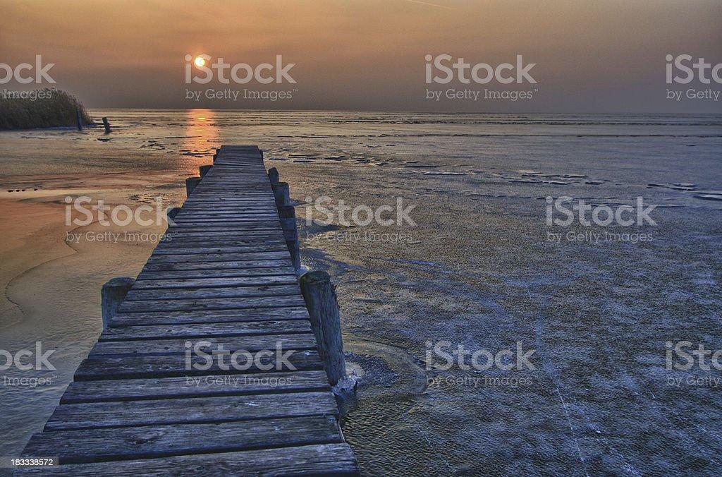Jetty on frozen lake in very last sunlight royalty-free stock photo