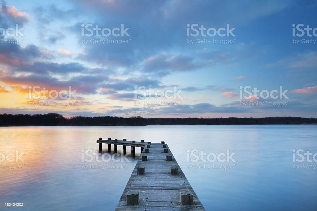Jetty on lake at sunset in Amsterdamse Bos, The Netherlands royalty-free stock photo