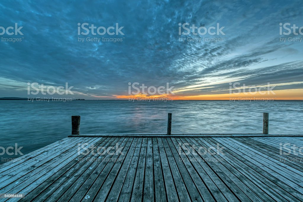 Jetty on lake with majestic cloudscape at sunset stock photo