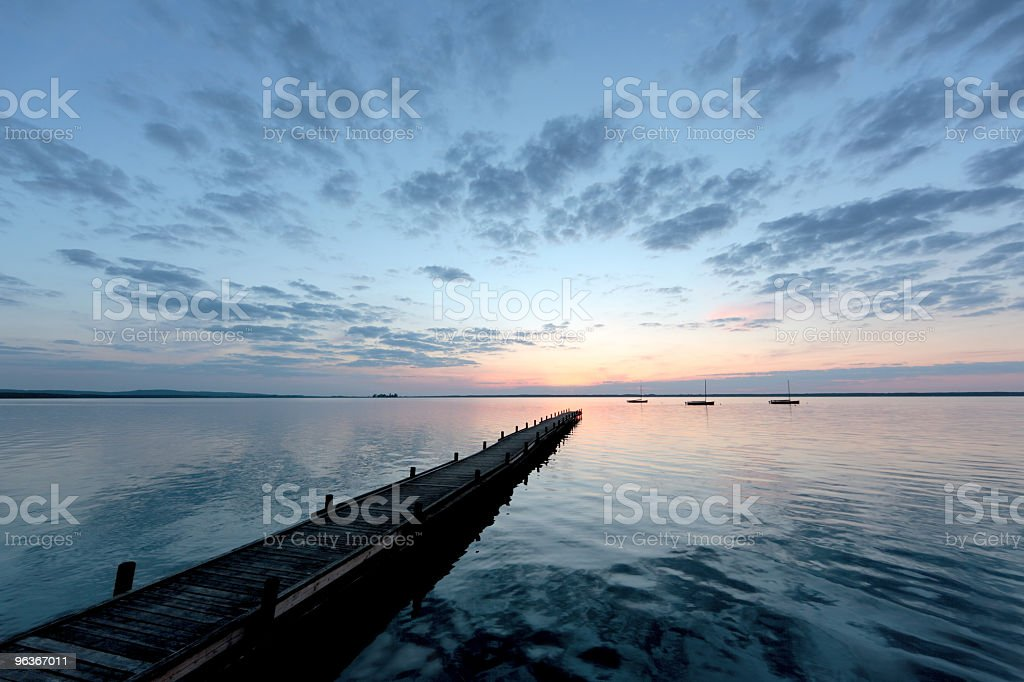 Jetty on lake with majestic cloudscape at sunset royalty-free stock photo