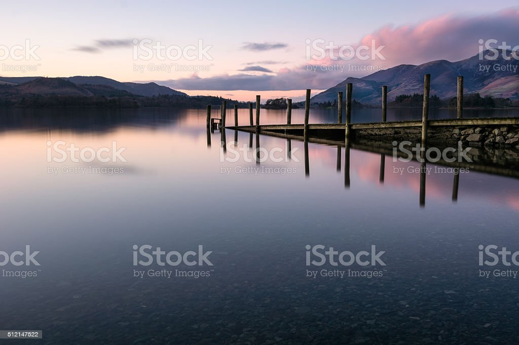 Jetty Reflections In Calm Lake With Pink Clouds In Sky. stock photo